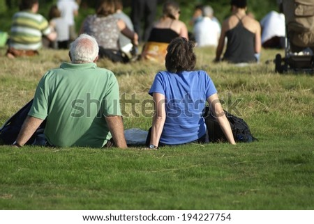 people sitting on grass during an outdoor event in a field