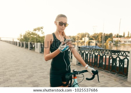 people, Sport and lifestyle concept - Beautiful girl walking in a warm day nature with a bike, a phone and headphones, pretty cute girl using smartphone beside her bike in park palms on a sunny day #1025537686
