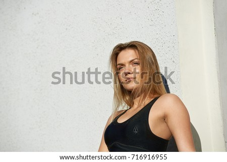 People, sports, fitness, active healthy lifestyle and determination concept. Beautiful determined young blonde female runner wearing stylish black sports bra, setting her mind up before marathon. #716916955