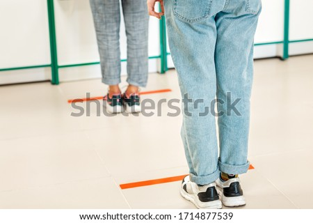 People stand in line, legs close-up. Attention line on the floor of the store to maintain social distance. Concept of the coronavirus pandemic and prevention measures