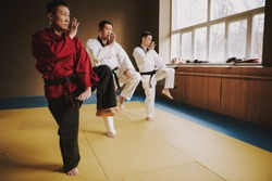 People stand in the hall and practice karate techniques together. A man in a red kimono stands with people who train in the gym.