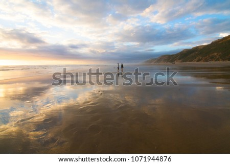 People stand on the beach at sunset in Northland, New Zealand