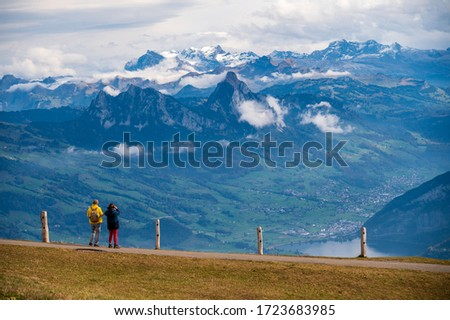Photo of  People standing at the view point at Rigi Kulm looking down to the mountains.  Rigi Kulm, Luzern, Switzerland.