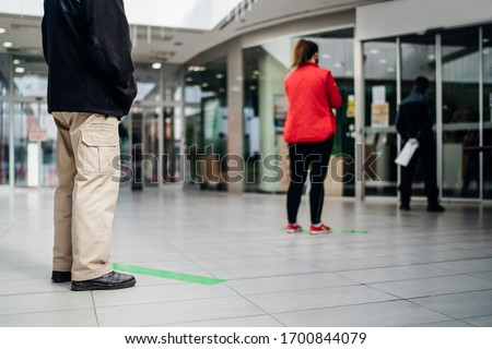 People standing in line front of bank/store due to coronavirus pandemic safety guideline.COVID-19 safe social distancing practice.Quarantine financial crisis,banking,loans.Spaced out queue.Crowd-limit