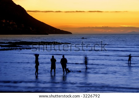 People standing in the ocean after sunset in Gordon's Bay, South Africa. Slow shutter speed results in some movement on people and the effect of foaming water.