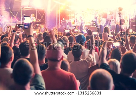 people standing with arms raised shoot a video on the phone at a street music show, blurred background
