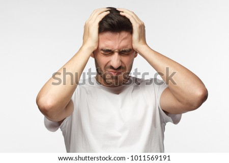 People, stress, tension and migraine concept. Upset unhappy young man squeezing head with hands, suffering from headache.