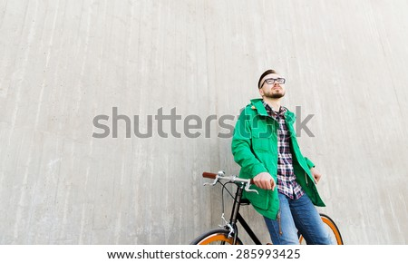 people, style, leisure and lifestyle - happy young hipster man with fixed gear bike on city street