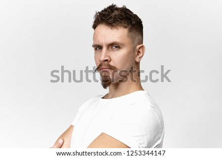 People, style, masculine beauty and fashion concept. Close up image of handsome hipster guy with penetrative look, stylish mustache and goatee beard, posing in studio, being proud of himself ストックフォト ©