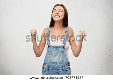 People, success, winning, victory, excitement, goals, determination and achievement concept. Joyful excited lucky student woman cheering, celebrating success, screaming yes with clenched fists #703971229