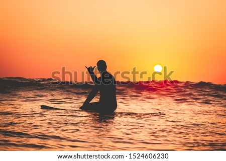 People surfing at the beach at sunset