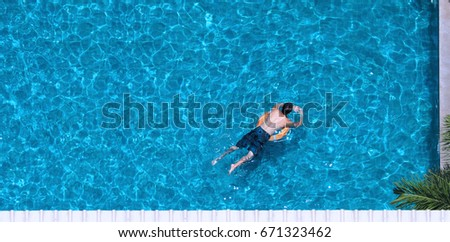 People swimming in the hotel pool in summer sunlight with blue color water and top view angle.