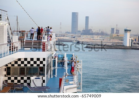 People take a rest at voyage on cruise ship at evening near city