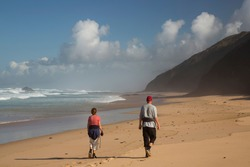 people taking a long walk on the sandy beach with coastal cliffs, high boisterous waves in the bay and damp slowly evaporating