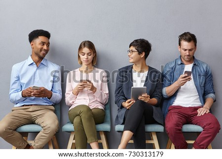 People, technology and communication concept. Four interracial people meet accidentaly in office bilduing, wait for meeting with boss, use electronic devices, enjoy pleasant lively conversation Stockfoto ©