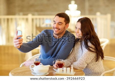 people, technology and dating concept - happy couple taking smartphone selfie and drinking tea at cafe or restaurant #392666923