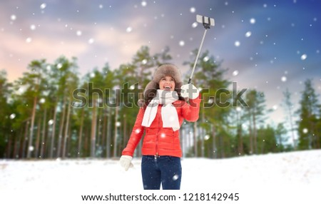 people, technology and leisure concept - happy woman in winter fur hat taking picture by smartphone selfie stick over winter forest background and show