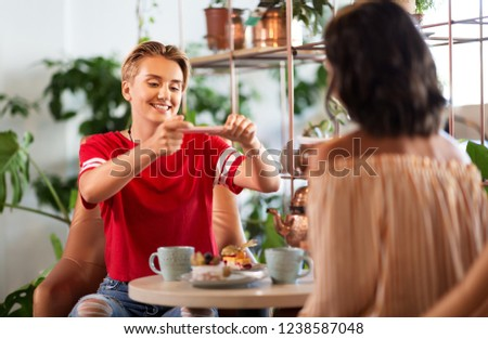 people, technology and lifestyle concept - female friends drinking tea and photographing food by smartphone