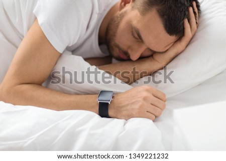 people, technology and rest concept - close up of man with smart watch sleeping in bed #1349221232