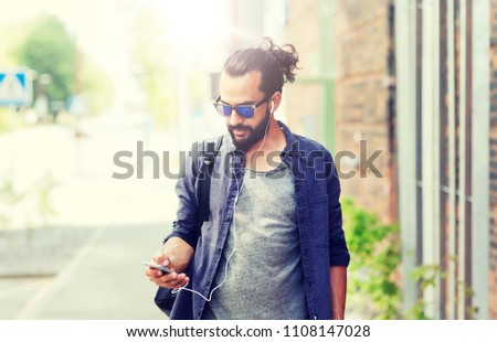 people, technology, travel and tourism - man with earphones, smartphone and bag walking along city street and listening to music