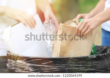 People throwing different types of garbage into litter bin outdoors, closeup. Recycling concept