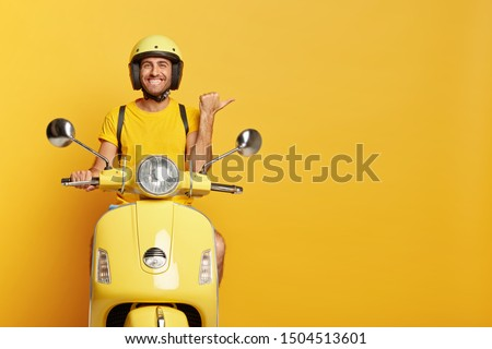 People, transport and advertisement concept. Cheerful young European male motorcyclist points thumb away, dressed casually, poses on own motorbike, glad to show copy space for your information