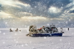People travel, dogsledding on the ice of frozen Baikal Lake in a safe and comfortable Hivus hovercraft.