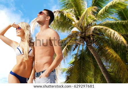people, travel, tourism and summer holidays concept - happy couple in sunglasses over exotic tropical beach with palm tree background #629297681