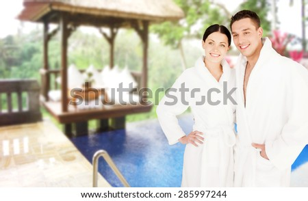 people, travel, tourism, vacation and honeymoon concept - happy couple in bathrobes over spa hotel resort background