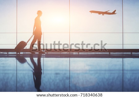 people traveling, silhouette of woman passenger with baggage in airport