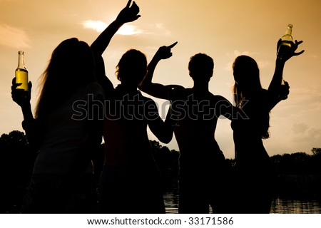 People (two couples) on the beach dancing to music, drinking and having a lot of fun in the sunset - only silhouette of people to be seen
