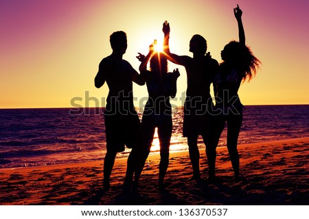 People two couples on the beach having a party drinking and having a lot of fun in the sunset only silhouette of people to be seen people having bottles in hands with the sun shining through