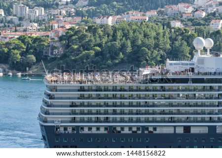 People, unrecognizable persons are enjoying a day at Adriatic sea on the top deck of the ship. Sea travel and relax #1448156822