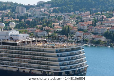 People, unrecognizable persons are resting on the top deck of the ship. Cruise ship docked at Dubrovnik, city on the Adriatic Sea. Sea travel and relax trip #1448156804