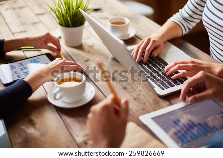 People using different devices at one table #259826669