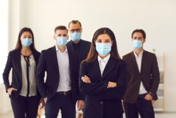 People vs coronavirus. Young business company manager and group of responsible employees care about customers and office coworkers wearing medical face masks at work due to the current world situation