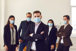 People vs covid. Young business company manager and team of responsible employees care about clients and coworkers wearing protective face masks in office due to the current epidemiological situation