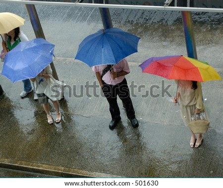 people waiting at busstop in the rain