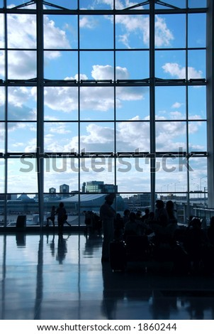 People waiting at the international airport terminal, bright blue sky outside