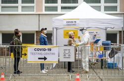 People waiting in covid-19 testing center outdoors on street, coronavirus concept.