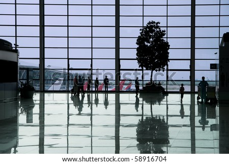 People waiting in the departure hall of a modern airport