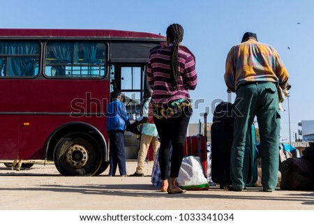 People waiting with luggage to embark on a bus from Dakar to Ziguinchor in Senegal, Africa.
