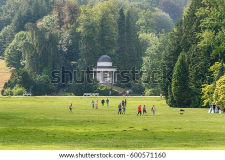 People walk in Karlsaue public park in Kassel, Germany. Jussowtempel is architecture of park. Travel photo