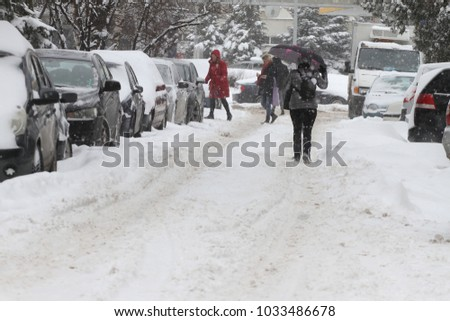 People walk on a very snowy sidewalk during snowstorm in the city of Sofia, Bulgaria – feb 26,2018. People step on an icy pathway, icy sidewalk. Uncleaned snow. #1033486678