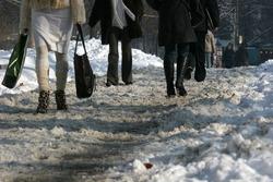 People walk on a very snowy sidewalk. People step on an icy pathway, icy sidewalk