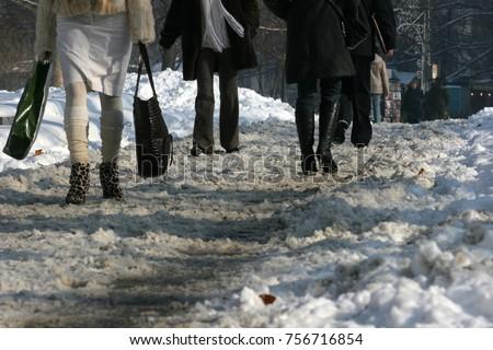 People walk on a very snowy sidewalk. People step on an icy pathway, icy sidewalk #756716854