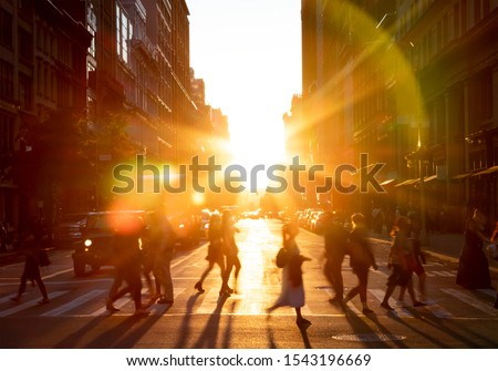 People walking across the street in New York City with the bright light of sunset shining between the buildings along 23rd St in Midtown Manhattan NYC