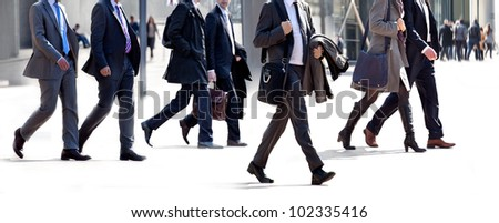 People walking against a light background. Walking businessmen against a background of an urban landscape.