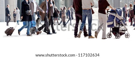 People walking against the light background of an urban landscape. Motion.