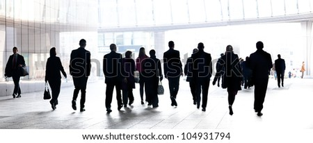 People walking against the light background of an urban landscape. Silhouettes.